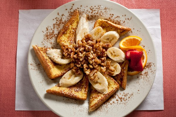 a picture of french toast with banana on top and cinamon